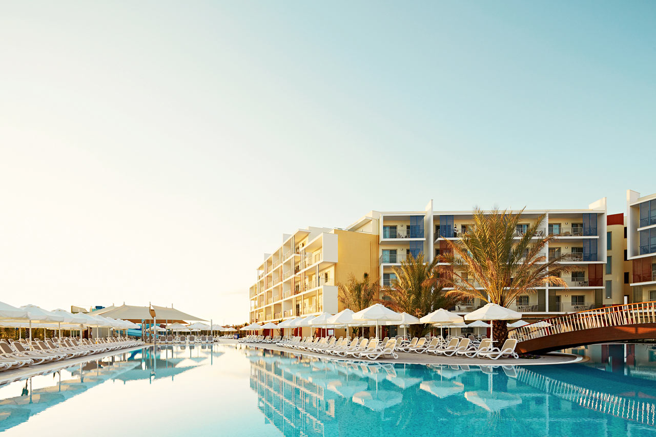 Stort poolområde med gott om solstolar och parasoller.
